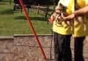 Dog Pushes Little Girl On Swings